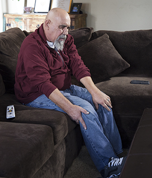 Man sitting on couch holding back of leg.