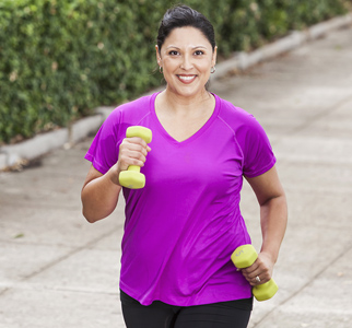 Woman jogging outdoors, carrying hand weights